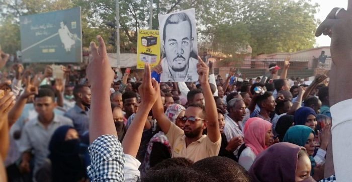 Protesters hold an image of teacher Ahmed al-Kheir, tortured and killed by Sudanese security forces - image: SPA via Facebook